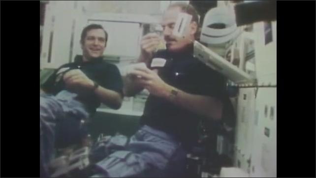 1980s: Astronauts float in space shuttle cabin.  Man eats.