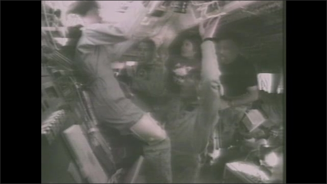 1980s: Astronauts work and move around space shuttle cabin.