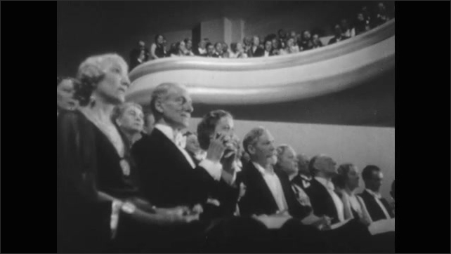 1940s: Formally dressed audience sits and stands.  Woman looks through opera glasses.