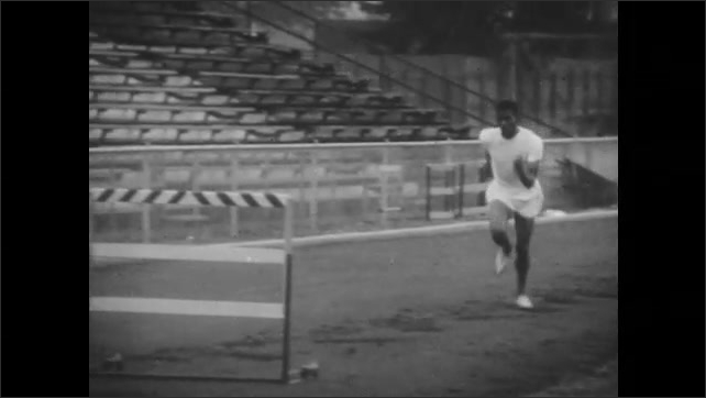 1950s: Man readies to run and begins running, jumping over hurdles. Man repeats run. He runs again until view freezes on his jump.