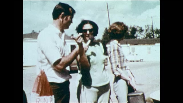 1970s: Woman speaks into microphone and gestures, then turns and points.