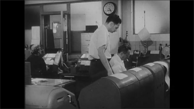 1950s: Man walks.  Man and woman sit in office.  Young women approach building.  People work in room of teletype machines.  Message is printed.