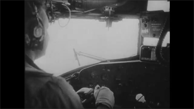 1950s: Airplane takes off.  Pilot in cockpit.  Plane flies through storm clouds.