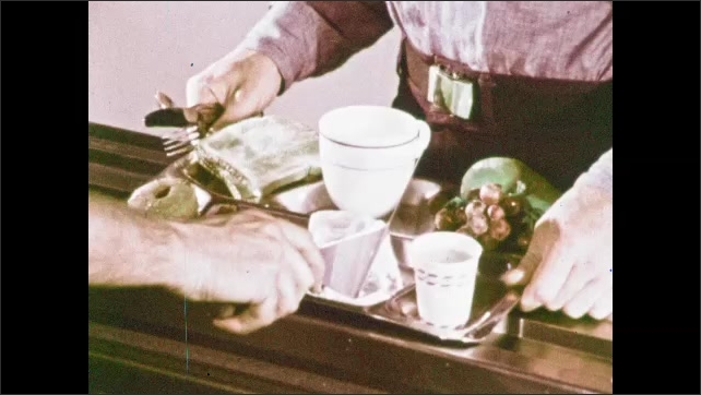 1970s: Man stands in front of cafeteria counter, holds tray. Worker scoops food onto tray. Man slides tray down shelf, worker slides omlet onto tray. Worker places food on tray.
