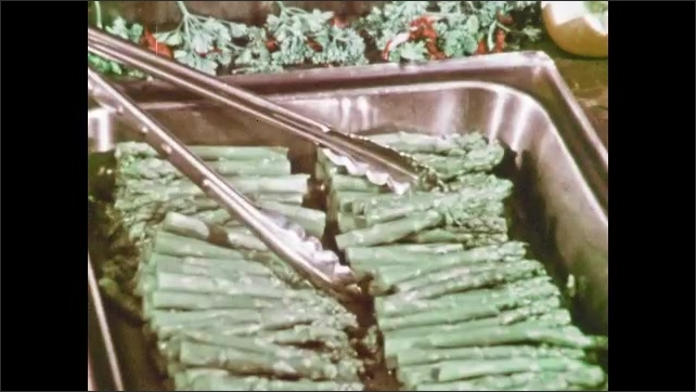1970s: Man stands in front of cafeteria counter, worker scoops food onto tray. Man places asparagus onto tray.