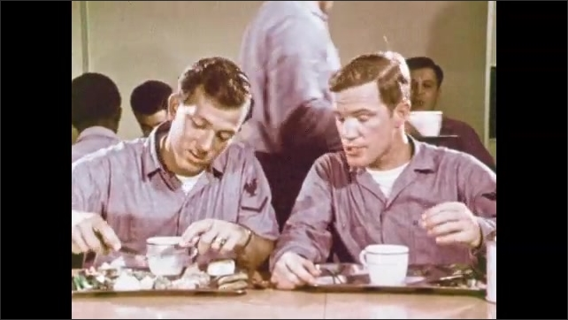 1970s: Man sits down next to other man, men talk, eat, drink. Man looks at watch, gets up, leaves. Man cuts up food on tray.