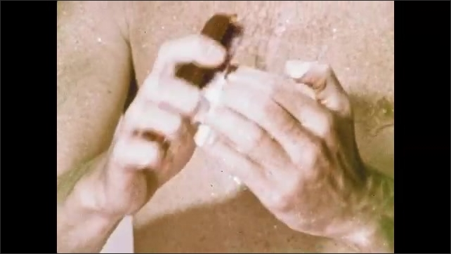 1970s: Man looks in mirror, touches face. Man in shower scrubs nails with brush, washes hair.