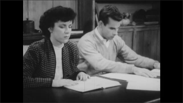 1940s: Boy and girl with eyes shut lean forward on table. Boy and girl raise eyebrows.