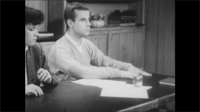 1940s: Hypnotized girl reaches across table and places glass of water in front of her.