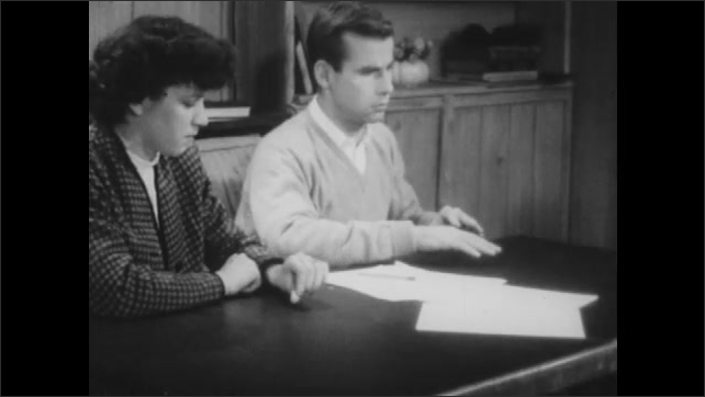 1940s: Hypnotized girl picks up pencil and touches boy's hand with it. Hypnotized boy flinches and draws hands from table. Boy places hands back on table.