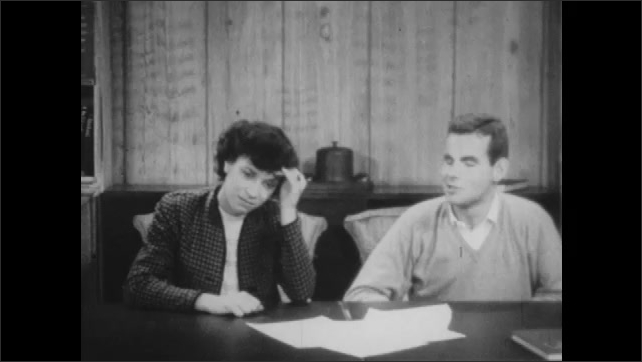 1940s: Man and woman sit at table, talk, answer questions from man off screen.
