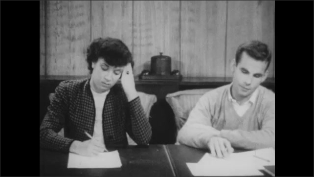1940s: Man and woman sit at table. Woman gathers paper in front of her, hands paper to man. Woman starts writing on paper. Man and woman talk.