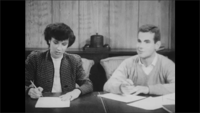 1940s: Man and woman sit table, write on paper. Man and woman talk, answer questions from man off screen.
