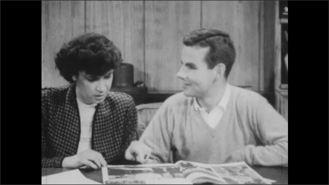 1940s: Man and woman sit at table, look at magazine. Man and woman talk, woman gets angry.