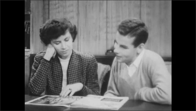 1940s: Man and woman sit at table, look at magazine, talk.