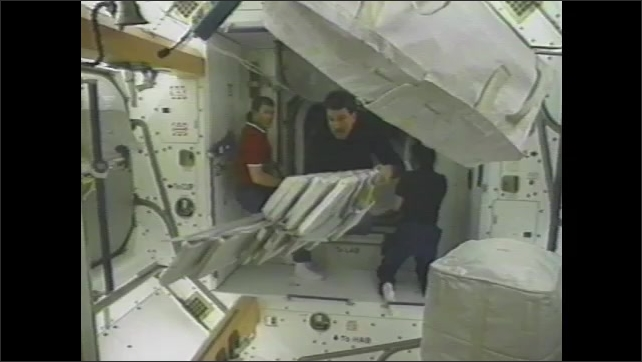 1990s: International Space Station hangs in orbit above Earth. Space station connects to space shuttle. Astronauts move supplies through corridor in space station.