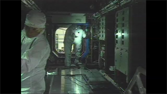 1990s: Engineers work on space laboratory component at warehouse. Men work on interior on laboratory module. Astronauts train on control panels. Metal rod points to buttons.