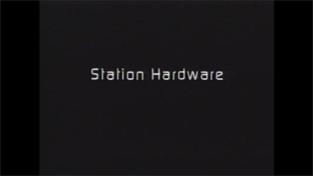 1990s: Man unfolds metal component. Men assist astronaut in donning gloves of space suit. Text on screen. Large plane lands on runway. Truck hauls equipment for space station.