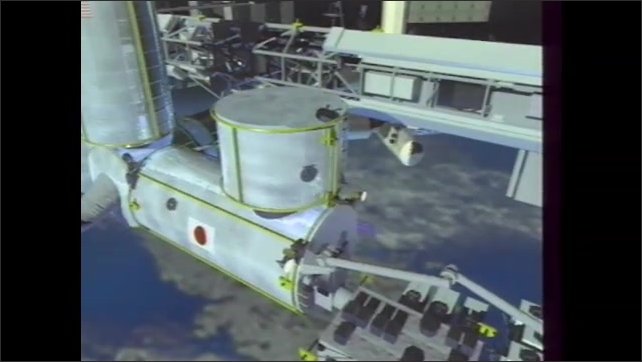 1990s: Experimentation module in Japanese processing facility. Robot arm adjusts components on ISS. Robot arm in Japanese processing facility.