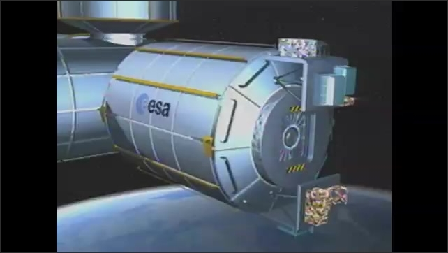 1990s: Computer animation of space station component construction. Engineers walk around space station components on floor of processing facility.