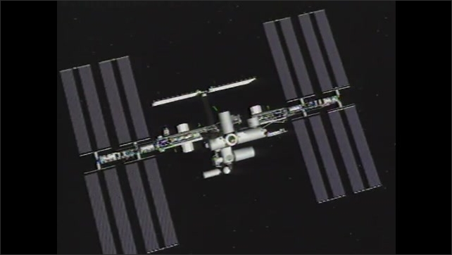 1990s: Lights blink on International Space Station. International Space Station zooms into distance. Bright star flies through night sky.