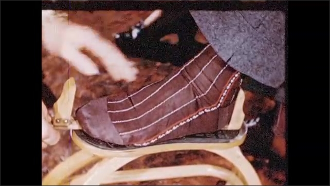 1940s: Man measures boy's foot.  Salesman puts shoe on customer's foot.
