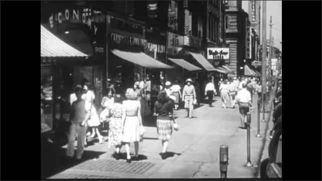 1940s: People walk down a crowded city sidewalk. Crowds of people on city sidewalk.