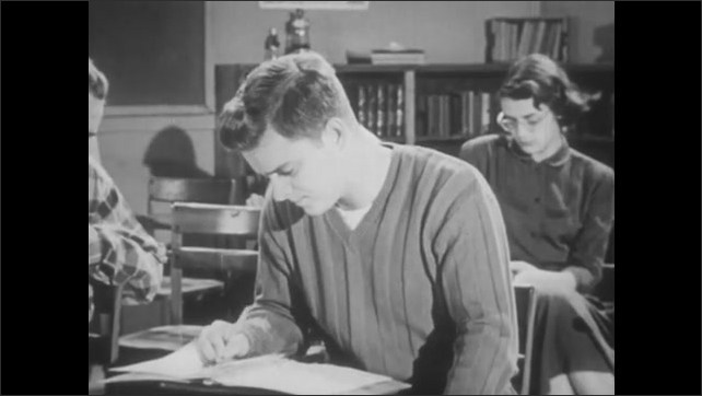 1950s: Girl at desk in classroom, tracking shot to boy writing, tracking shot to girl writing.