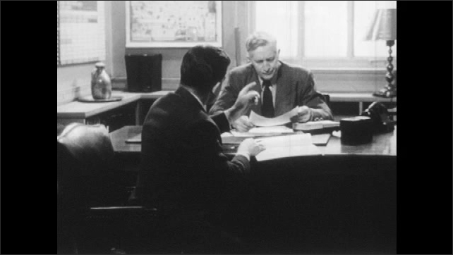1950s: Two men talk at desk. Woman leans over couch while men talk about brochure.