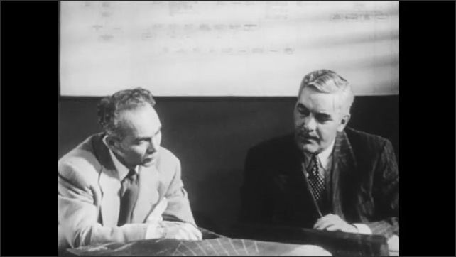 1950s: Two men talk and look at blueprints.
