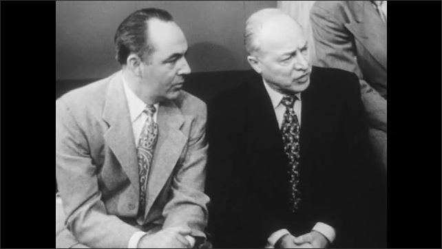 1950s: Two men sitting on couch talk to man sitting at desk.
