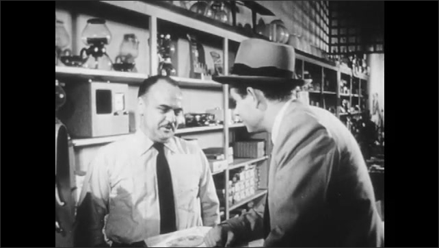 1950s: Salesman tries to make sale at appliance store.