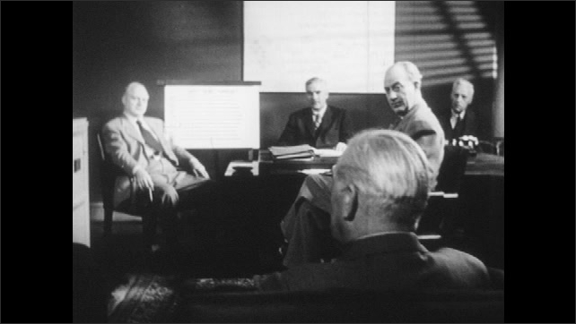 1950s: Men discuss next year's forecast chart.