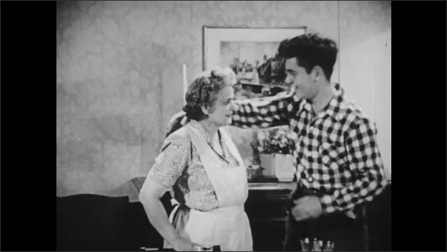 1950s: Teenage boy and woman holding hands. Woman talks to boy as he sets glasses on dinning table. Boy kisses woman on forehead. Woman leaves. Boy thinks to himself.