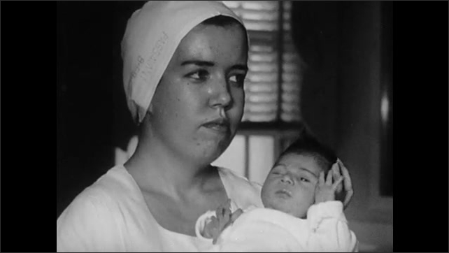 1950s: Man and woman walk up to glass door, point and make faces t something inside. Woman holds baby, forlorn. Man and woman at glass door. Woman holding baby.