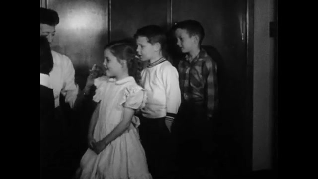 1950s: Various vaccines in glass bottles. Children stand in line. Men and women walk out of door holding envelopes.