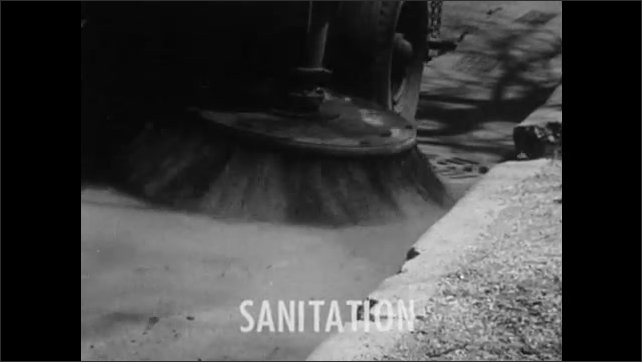 1950s: Street cleaning vehicle drives down road as brushes clean. The word Sanitation appears. Poster on wall for Stop Disease.