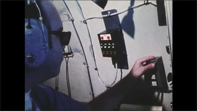 1970s: UNITED STATES: earth scientists inside plane cabin. Man operates button. Containers fired into clouds