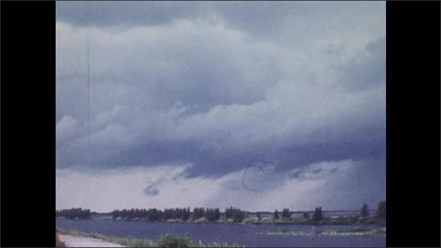 1970s: UNITED STATES: engine of plane during flight. Plane in sky. Rain clouds in sky. Man measures precipitation from car