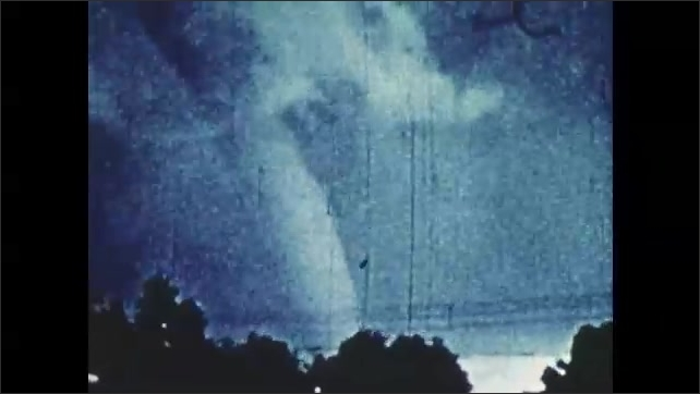 1970s: UNITED STATES: tornado air column spins. Tornado damage to home. Man enters house during storm