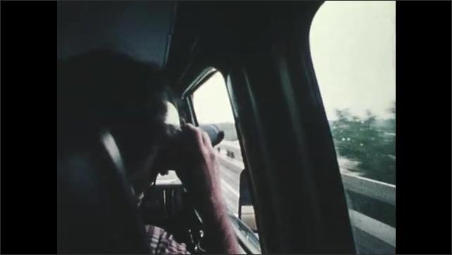1970s: UNITED STATES: van drives along road during tornado. Tornado air column crosses ground. Man photographs tornado from moving vehicle