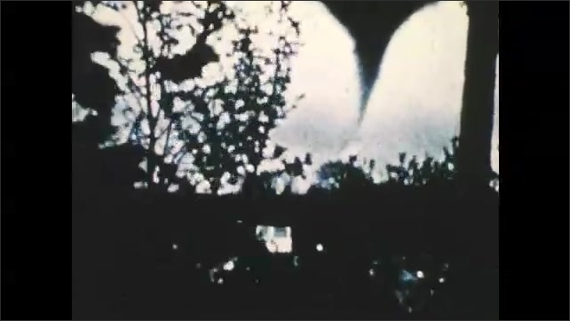 1970s: UNITED STATES: Earth Scientists watch storm development on monitor. Tornado crosses ground