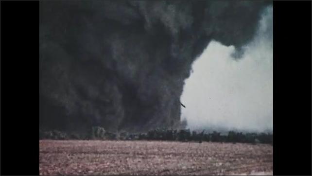 1970s: UNITED STATES: Tornado crosses landscape. Air column spins.