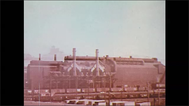 1970s: UNITED STATES: man stands inside metal building on industrial site. Industrial building by waterway. Man in laboratory pours water into experiment