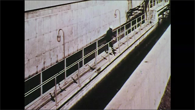 1970s: UNITED STATES: water filters through purification plant. Water in tanks. Sedimentation tank. Water by industrial building. Water in damn