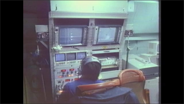 1970s: Man at control panel. People on control room. Man looking at monitor. Men with headsets.