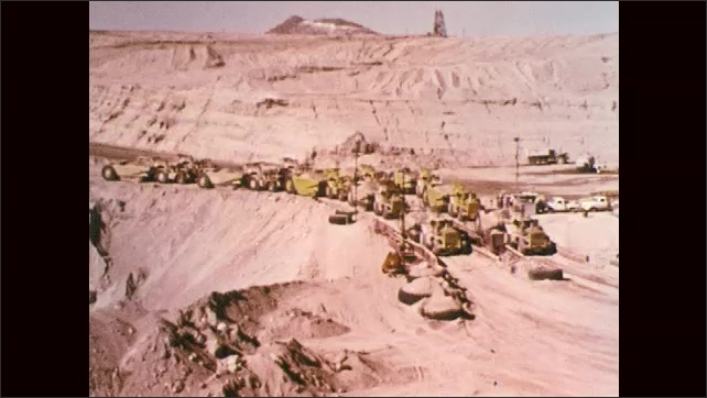 1970s: Expansive view of open mine area in mountains. Heavy equipment line up along road. String of explosions, dust billows.
