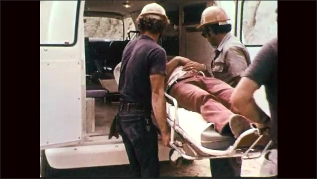 1970s: Woman in hard hat looks serious. Men carry away bloodied man on stretcher, people stand watching. Men load stretcher into ambulance, shut doors. Man climbs into cab.