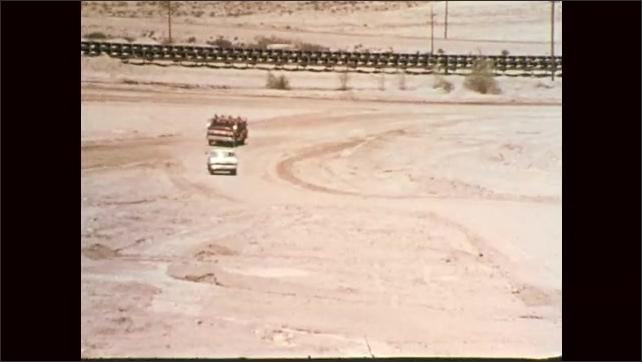1970s: Man in hard hat behind wheel of ambulance talks on radio. Trucks drive across flat, barren landscape.