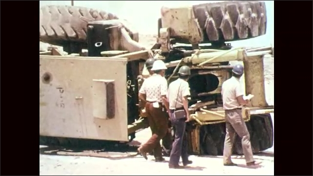 1970s: Mine site, men in hard hats walk towards overturned front end loader, investigate, peer inside, point. Men walk around side. Man climbs in. Man brushes off hands.